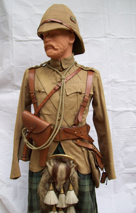 "A Captain of the Argyll & Sutherland Highlanders as he might have appeared in South Africa 1899-1902. He wears a khaki drill doublet with gauntlet cuffs, helmet with  khaki 6 panel cover and regimental badge or ""flash"" on  the left side consisting of an o/r's collar badge on a red  Melton cloth backing. His beautiful honey colored Sam Browne belt, haversack, water bottle are all provided by Hobson and Sons, and his helmet is by Hawkes & Co. (Photo: James Holt collection)"