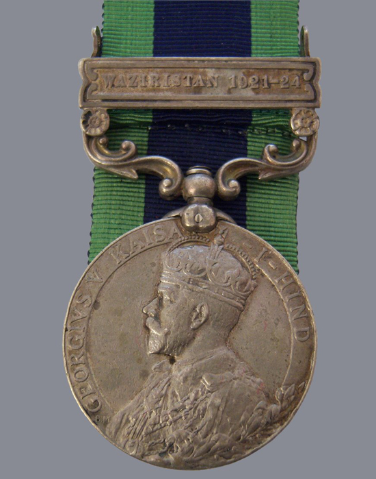 An example of the India General Service medal 1908 with the Waziristan clasp. This shows the obverse with the image of King George V in coronation robes. This example was struck at the Calcutta mint as is indicated by the less ornate claw than the one seen on the Royal Mint struck medals. (Photo courtesy of Brian Wolfe)