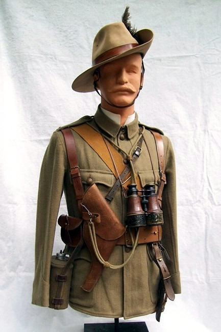 Officer's four pocket serge frock of the Imperial Yeomanry. Five bronze Imperial Yeomanry buttons secure the front of the frock while a pair of  bronze IY shoulder titles adorn his shoulder straps. He carries field glasses, private purchase haversack and one of many types of private purchase water bottles available. The felt slouch hat is made by Thomas Townend and Sons. Stitched to the crown of the hat, hidden by the upturned brim, is a brass holder to accommodate his Emu feather plume. (Photo: James Holt collection)
