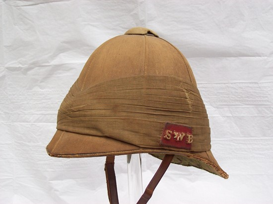 Officer's foreign service helmet worn in South Africa by Capt. William H. G. Kemmis 4th Vol.Battalion South Wales Borderers. Khaki covered cork with muslin puggaree. The flash is a leather backed red Melton cloth with the individual letters sewn to the backing. (Photo: James Holt collection)