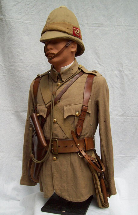 Infantry officers serge frock as per Dress Regulations for Officers 1900, made exactly as the cotton drill version with the exception of larger seams to accommodate the thicker material. The serge for both officers and men was warmer and more durable than the cotton drill frocks. His white foreign service helmet has a separate khaki cover and puggaree which bears the regimental flash of the Shropshire Light Infantry, (white worsted embroidery on a red cloth backing). His double brace Sam Browne belt would carry his revolver and sword. Strung over his shoulders, haversack and private purchase water bottle. (Photo: James Holt collection)