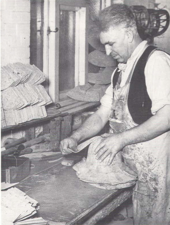 A vintage photo of a cork helmet being produced, this process involved sheets of cork that were shaped on a block and glued together. This process was known as knocking-on. The rough shaped shells then went to a blocking machine to refine the shape of the helmet before being covered with the canvas fabric.