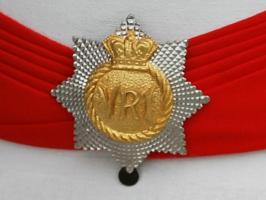 A close up of the Royal Canadian Regiment puggaree slider badge on the modern full dress Wolseley helmet.