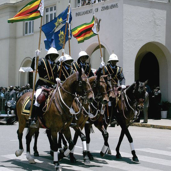 In Zimbabwe's capital, Harare, presidential guards on horseback trot past parliament at its official opening by President Robert Mugabe.
