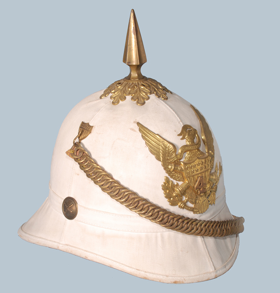 "An example of the M1887 helmet, which seems to have been ""painted"" with Blanco to give it a fresh white look. This helmet features the brass hardware, including spike and base, chinchain, helmet plate and side buttons that were worn with the dark blue/black dress helmet. While against official regulations it seemed it was common for officers to wear the accoutrements on these helmets."