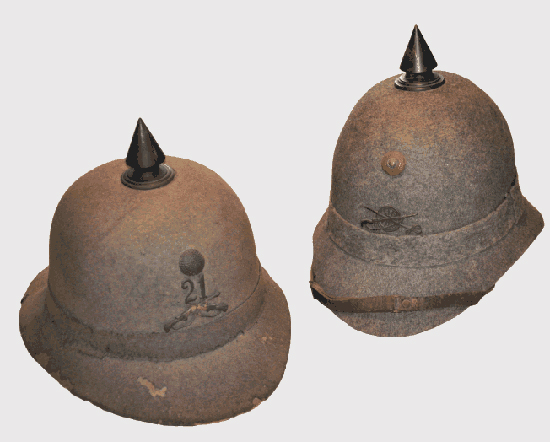 "Fig 4: On the left: a 1911 Infantry officers' helmet ""updated"" to the 1913 model. Notice the lower skull and the type of construction with felt over stiffened cloth. Also notice the non-pierced metal ""Kokarde"". On the right: a 1913 Military Administration officers' helmet. Notice the blackened metal (copper) spike and the official pressed leather ""Kokarde""."
